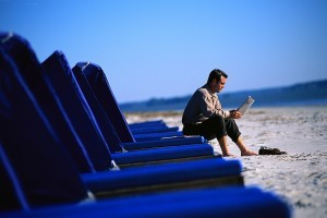 Man Reading Newspaper at Beach